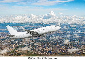 Passenger white airplane flies climbing over a large megaopolis, city.