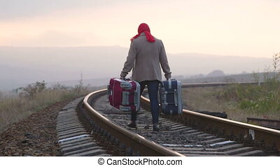 Passenger with suitcase walking down railroad track