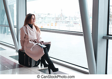Passenger woman in airport waiting for air travel.