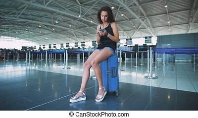Passenger, woman in the airport, waiting for her flight.