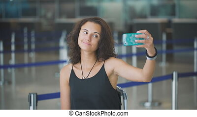 Passenger, woman in the airport, waiting for her flight making selfie with he smiling face
