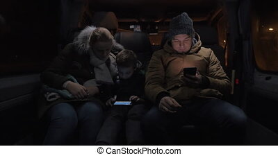 Passengers in minibus passing the time with cellphones