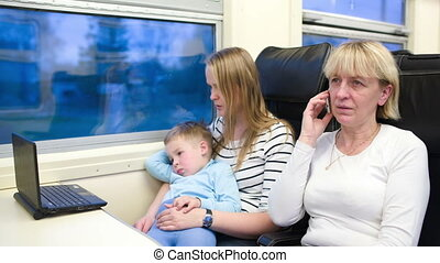 Passengers in the train watching video on laptop and talking on the phone