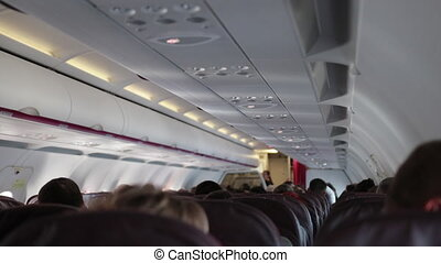 Passengers of economy class sit calmly in cabin of airplane.