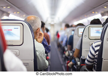 Passengers on the airplane. - Interior of airplane with...