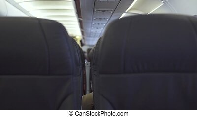 Passengers seats in economy class modern airplane while flying in sky. Passengers chairs inside cabin commercial plane while flight. People traveling by modern commercial airplane.
