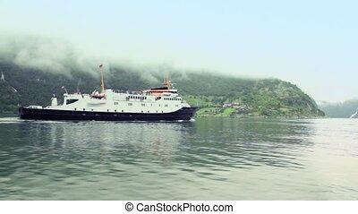 Passengers ship float in fiord at background of coastal village