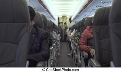 Passengers sitting on seats aircraft while flying in sky. Passengers inside cabin commercial plane while flight. Air traveling by modern commercial airplane.