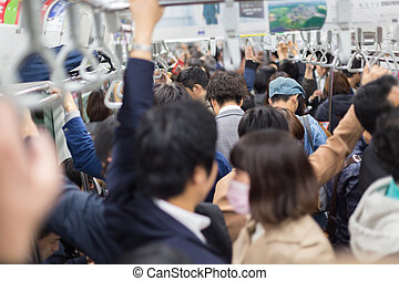 Passengers traveling by Tokyo metro. Business people...