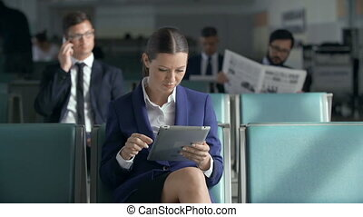 Focus on business woman with digital tablet waiting for a flight, other passengers in the background