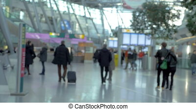 Passengers walking around big and light airport hall