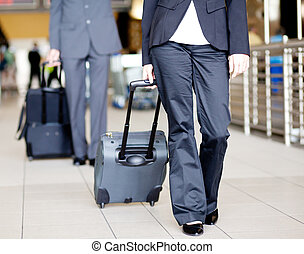 passengers walking in airport with luggage