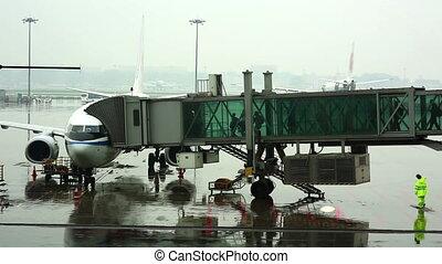 passengers walking on boarding bridge at airport jetway