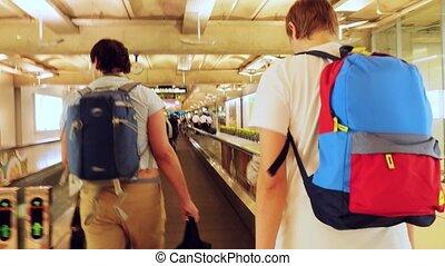 Passengers with backpacks on travelator in international airport. 3840x2160, 4k