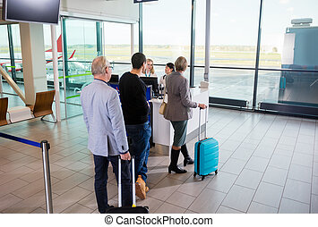 Passengers With Luggage Waiting For Their Turn At Airport Recept