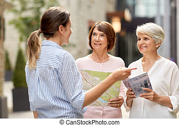 passerby showing direction to senior women in city