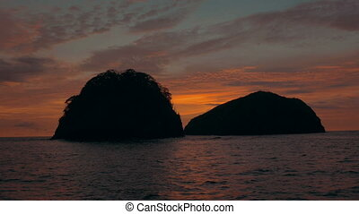 Passing a tropical island cluster at sunset - Establishing...