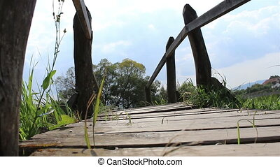 Passing A Wooden Footbridge - A man wearing sandals is...