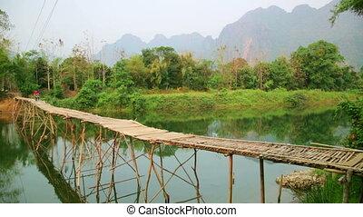 Passing bamboo bridge by motorbike, limestone view, laos