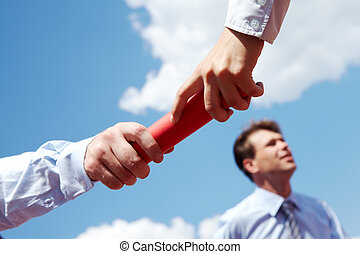 Photo of business people hands passing baton during race