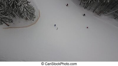 Passing by skiers in the mountains in the forest on ski resort. Aerial view