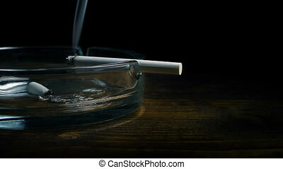 Moving slowly past a smoking cigarette on ash tray