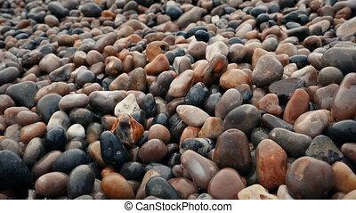 Tracking shot moving slowly over many wet pebbles