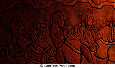 Medieval stone wall with carving artwork of men riding horses