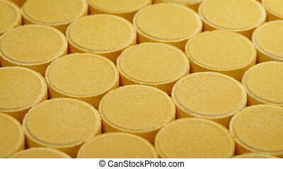 Passing Rows Of Vitamin Pills Closeup - Passing rows of...