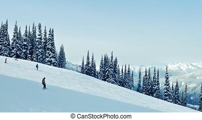 Passing Slope As Family Snowboards - Passing a snowy ski...