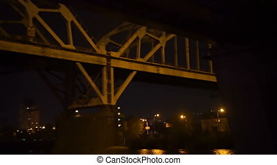 Passing the river railway bridge at night