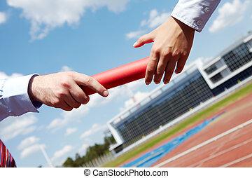 Photo of business people hands passing baton during marathon