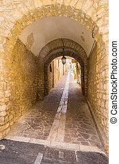 Passing under stone arches to a small alley
