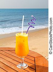 passion fruit juice with ice on the table against the background of sea and sky