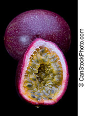 Passion Fruit - Whole and sliced passion fruit on black...