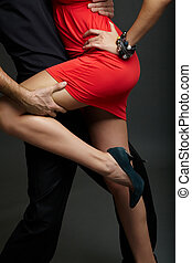 Passion - Man holds leg of female in red dress and high-...
