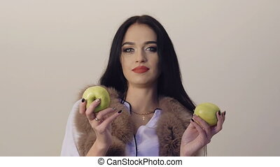 Passionate brunette posing and going around with two green apples. Slowly