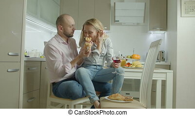 Passionate couple enjoying lunch in domestic kitchen -...