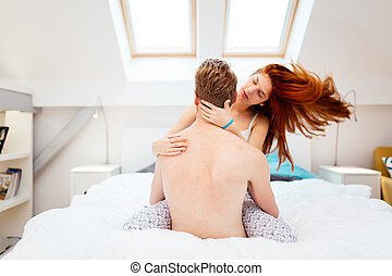 Passionate couple foreplay in bed