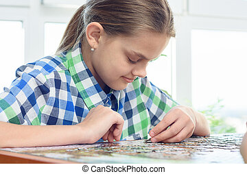 Passionate girl collects puzzles at home at the table