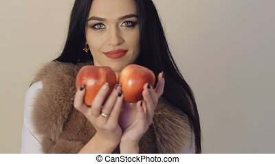 Passionate girl going around and smiling to camera with two red apples Slowly