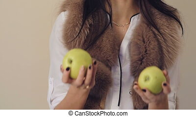 Passionate girl smiles and throws up two green apples, looks...