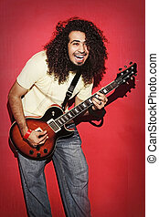 Passionate guitarist laughing with joy long curly hair playing guitarist