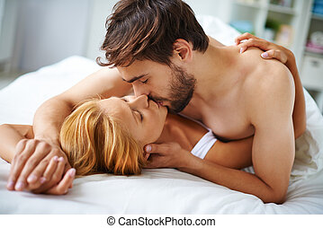 Passionate kiss - Passionate couple lying on bed and kissing