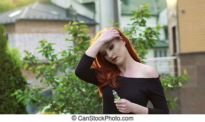 Passionate lady smoking e-cigarette on the street. Slowly