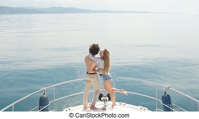 Passionate lovers dancing on bow of deck while sailing on...