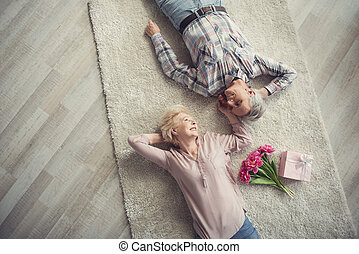 Passionate mature couple resting on the floor