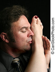 Passionate Moment - A handsome man kissing a woman's foot.