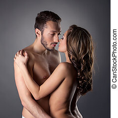 Passionate nude lovers embracing in studio