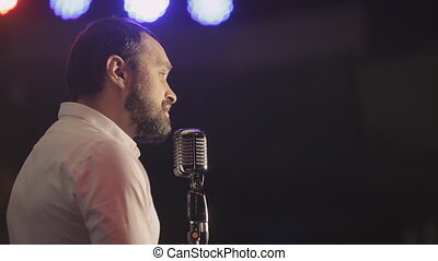 Passionate singing of the man in retro microphone